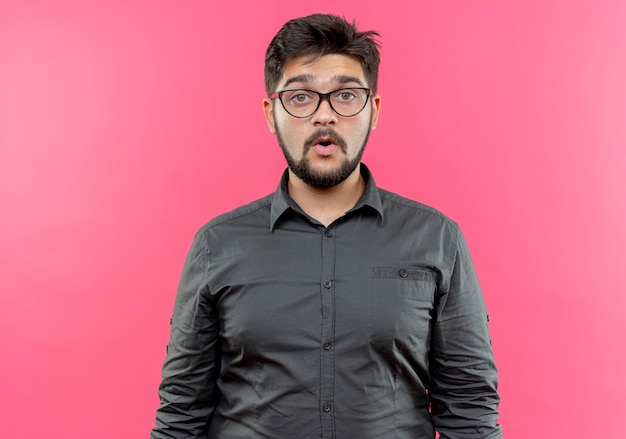 Onder de indruk jonge zakenman die een bril draagt die op roze muur wordt geïsoleerd