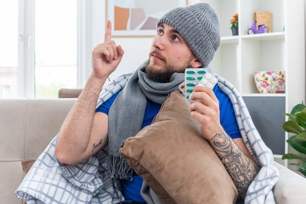 Onder de indruk jonge zieke man met sjaal en wintermuts gewikkeld in deken zittend op de bank in de woonkamer met kussen en pakjes pillen kijkend en omhoog wijzend