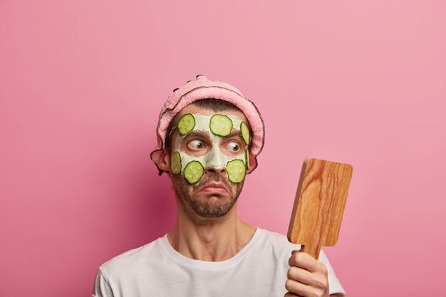 Onder de indruk jongeman staart naar houten spiegel, past kleimasker en komkommers toe, geschokt door veel rimpels op de teint