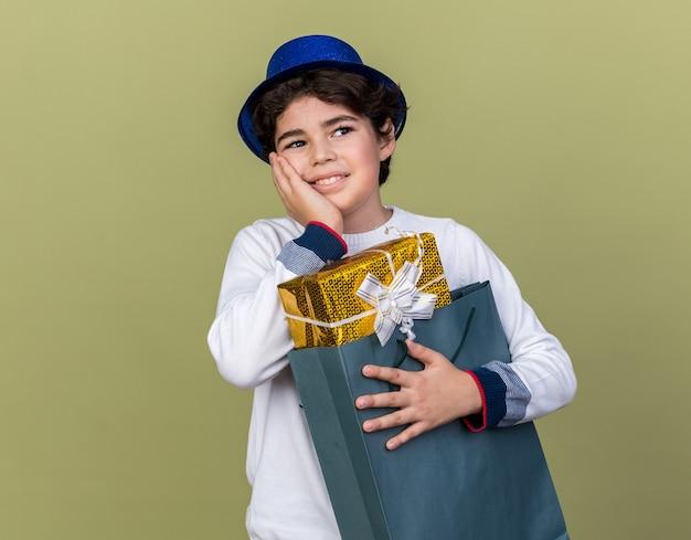 Onder de indruk jongetje met een blauwe feestmuts die een cadeauzakje vasthoudt en zijn hand op zijn wang legt