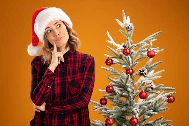 Onder de indruk kantelend hoofd jong mooi meisje dat in de buurt van de kerstboom staat met een kerstmuts die de vinger op de wang zet die op een oranje achtergrond wordt geïsoleerd