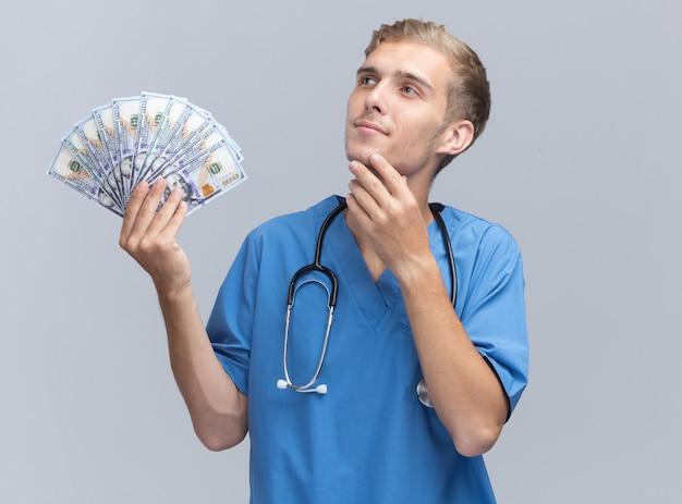 Onder de indruk kijken naar kant jonge mannelijke arts arts uniform dragen met een stethoscoop houden geld zetten hand onder de kin geïsoleerd op een witte muur