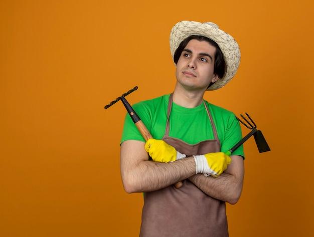 Onder de indruk kijken naar kant jonge mannelijke tuinman in uniform dragen tuinieren hoed met handschoenen houden en kruising schoffel hark met hark geïsoleerd op oranje met kopie ruimte