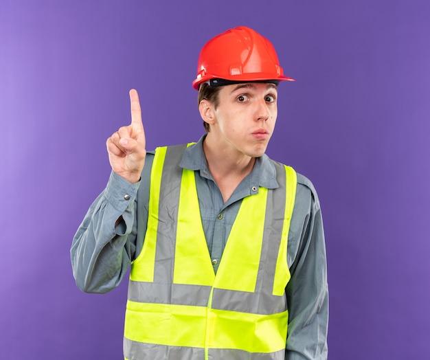 Onder de indruk kijkend naar camera jonge bouwer man in uniforme punten naar boven