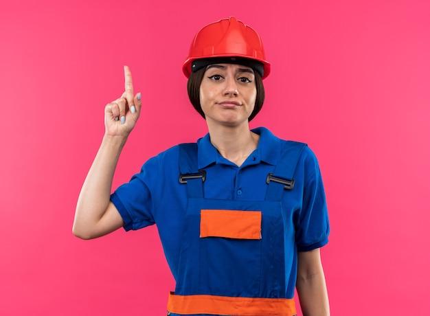 Onder de indruk kijkend naar camera jonge bouwer vrouw in uniform duim opdagen