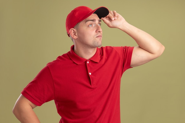 Onder de indruk kijkend naar de jonge bezorger aan de zijkant met uniform en pet en met pet geïsoleerd op olijfgroene muur