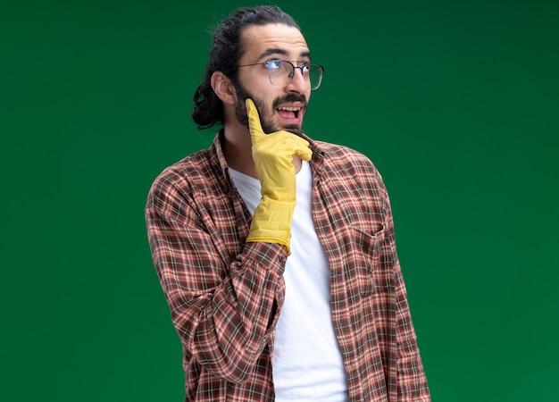 Onder de indruk kijkend naar de jonge, knappe schoonmaakster met t-shirt en handschoenen, greep kin geïsoleerd op groene muur