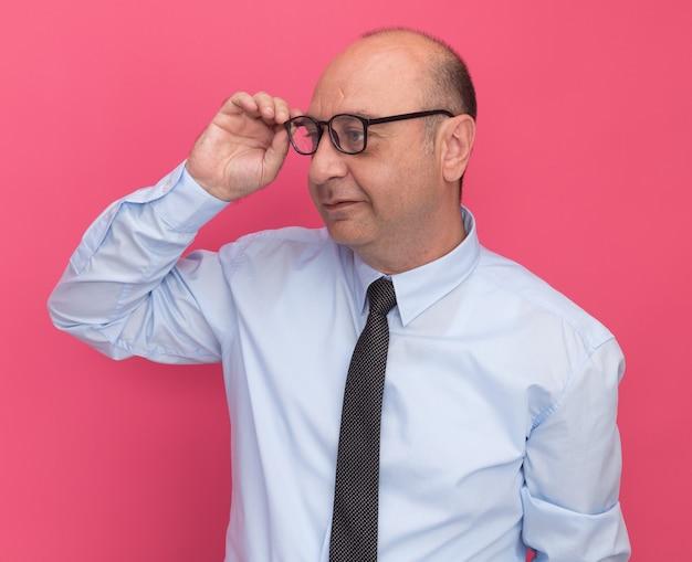 Onder de indruk kijkend naar een man van middelbare leeftijd met een wit t-shirt met stropdas en een bril geïsoleerd op een roze muur