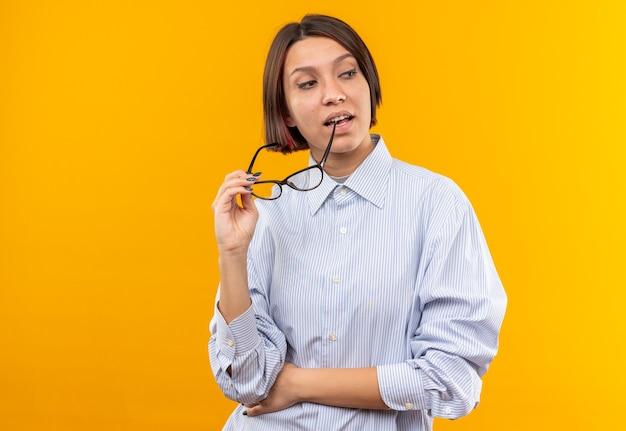 Onder de indruk kijkende jonge mooie vrouw die een bril draagt die op een oranje muur is geïsoleerd