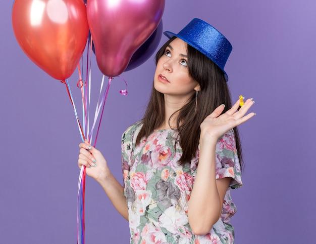 Onder de indruk kijkende jonge, mooie vrouw met een feestmuts met ballonnen die hand geïsoleerd op een blauwe muur verspreiden