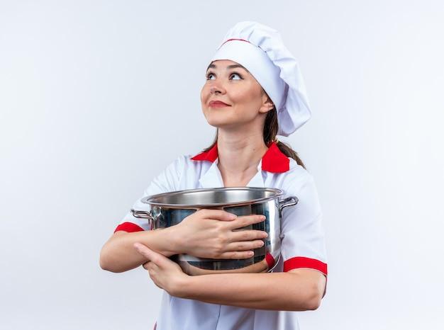 Onder de indruk kijkende jonge vrouwelijke kok die een chef-kokuniform draagt met een steelpan die op een witte muur wordt geïsoleerd