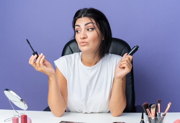 Onder de indruk kijkende mooie vrouw zit aan tafel met make-uptools met mascara