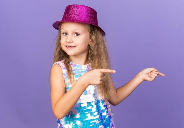 Onder de indruk klein blond meisje met violette feestmuts wijzend naar kant geïsoleerd op paarse muur met kopie ruimte