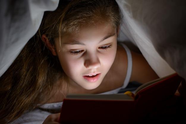 Onder de indruk klein meisje onder de deken met een boek en een zaklamp lezen verschrikkingen voordat ze naar bed gaan