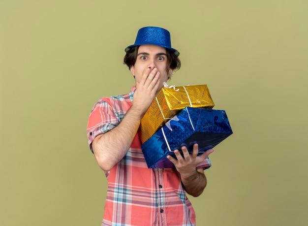 Onder de indruk knappe blanke man met blauwe feestmuts legt hand op mond en houdt geschenkdozen vast
