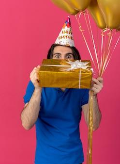Onder de indruk knappe blanke man met verjaardagspet houdt heliumballonnen en geschenkdoos vast