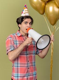 Onder de indruk knappe blanke man met verjaardagspet houdt heliumballonnen en luidspreker vast