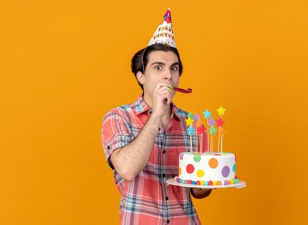 Onder de indruk knappe blanke man met verjaardagspet houdt verjaardagstaart blazend feestfluitje