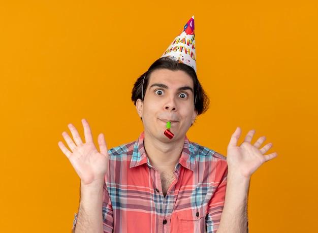 Onder de indruk knappe blanke man met verjaardagspet staat met opgeheven handen die feestfluitje blazen