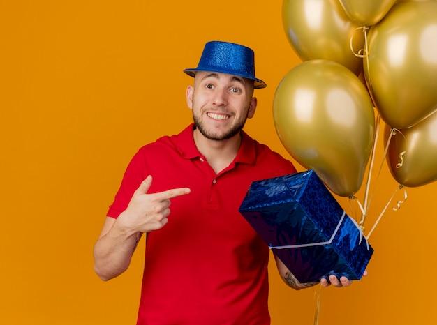 Onder de indruk lachende jonge knappe slavische feestjongen die feestmuts draagt ?? die ballonnen en cadeaupakket houdt kijkend naar camera wijzend op cadeaupakket geïsoleerd op een oranje achtergrond