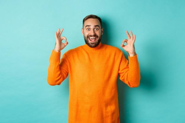 Onder de indruk man die iets geweldigs prijst, oké tekenen vertoont en verbaasd kijkt, staande in een oranje trui op een lichtblauwe achtergrond.