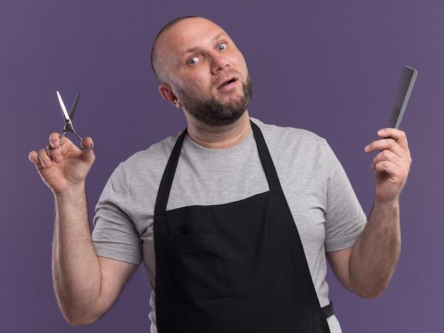 Onder de indruk mannelijke kapper van middelbare leeftijd in uniform bedrijf schaar met kam geïsoleerd op paarse muur