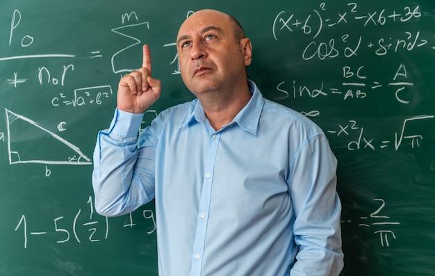 Onder de indruk mannelijke leraar van middelbare leeftijd die vooraan op het schoolbord staat wijst naar omhoog