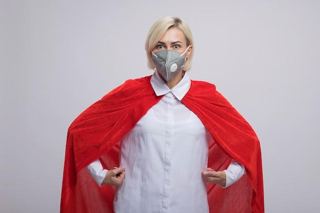 Onder de indruk middelbare leeftijd blonde superheld vrouw in rode cape met beschermend masker staande als superman geïsoleerd op een witte muur