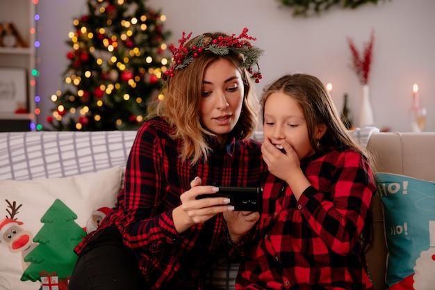 Onder de indruk moeder en dochter kijken naar iets op telefoon zittend op de bank en genieten van kersttijd thuis