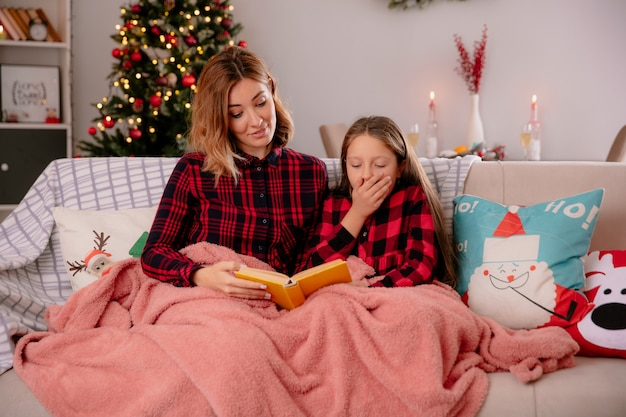 Onder de indruk moeder en dochter leesboek bedekt met deken zittend op de bank en genieten van kersttijd thuis