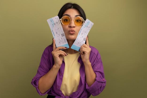 Onder de indruk mooie brunette vrouw in zonnebril houdt vliegtickets dicht bij het gezicht geïsoleerd op olijfgroene muur