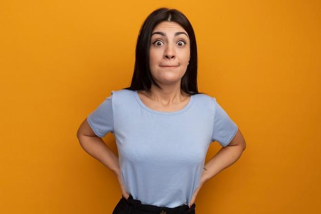 Onder de indruk mooie brunette vrouw legt handen op taille en kijkt naar voorzijde geïsoleerd op oranje muur