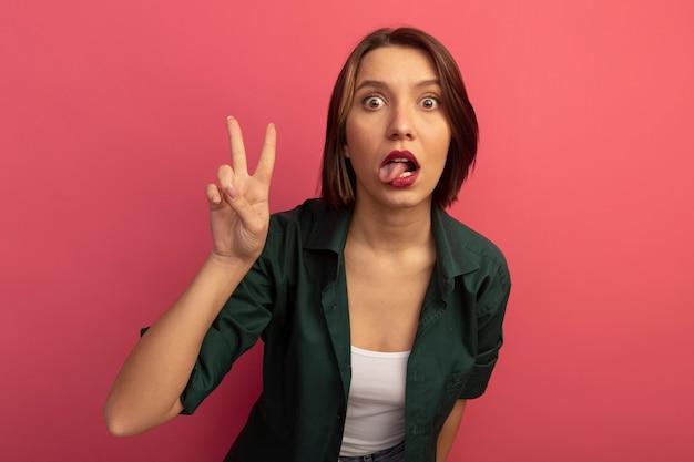 Onder de indruk mooie vrouw steekt tong uit en gebaren overwinning handteken geïsoleerd op roze muur