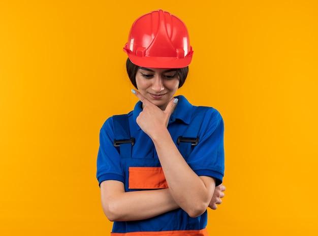 Onder de indruk neerkijkend op jonge bouwvrouw in uniform die hand op de kin legt
