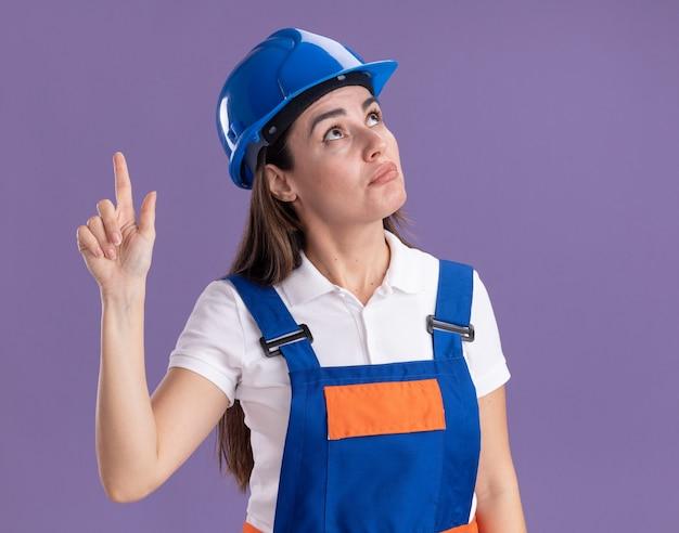 Onder de indruk op zoek naar jonge bouwersvrouw in uniforme punten omhoog geïsoleerd op paarse muur