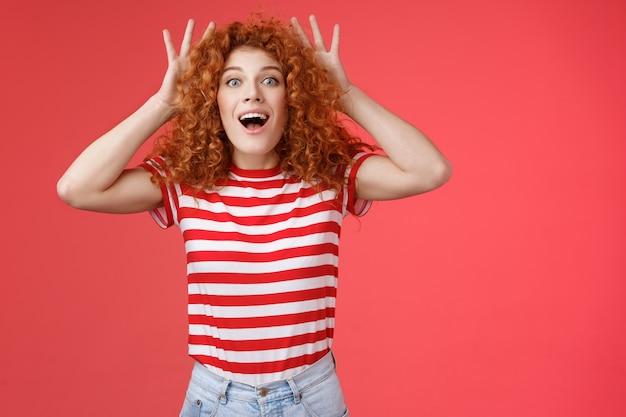 Onder de indruk opgewonden geschokte jonge schattige roodharige gember vriendin met krullend haar reageert verbaasd verrast geweldig cadeau kan niet geloven dat eigen ogen hoofd grijpen opgewonden open mond in een hinderlaag gelokt rode achtergrond.