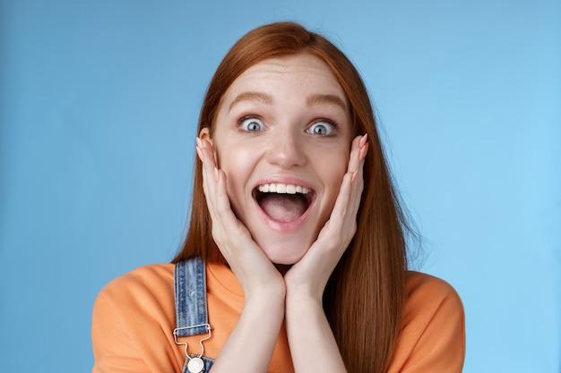 Onder de indruk opgewonden overweldigd jonge roodharige vriendin fan schreeuwen opgewonden uitdrukkelijke genegenheid aanbidden geweldige muziekband schreeuwen vrolijk reageren verrast verbaasd staan blauwe achtergrond