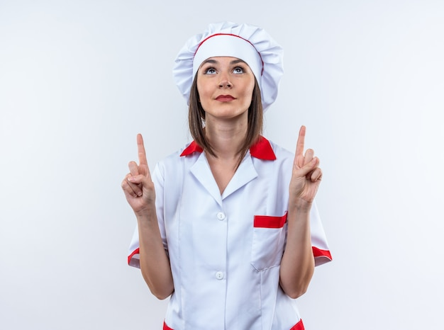 Onder de indruk opzoeken van jonge vrouwelijke kok die chef-kok uniforme punten draagt naar omhoog geïsoleerd op een witte muur