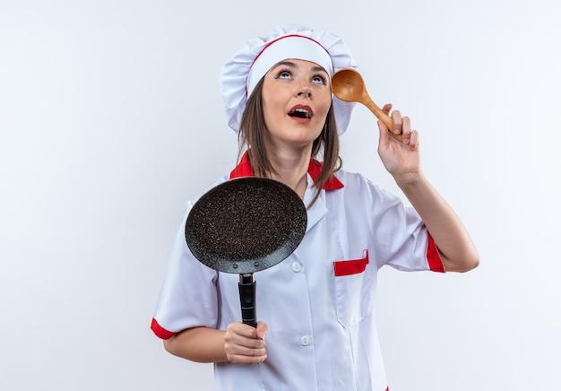 Onder de indruk opzoeken van jonge vrouwelijke kok in uniform van de chef-kok met koekenpan met lepel geïsoleerd op een witte achtergrond