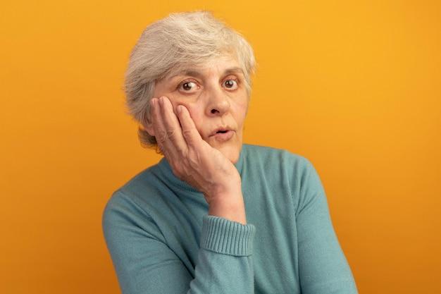 Onder de indruk oude vrouw die een blauwe coltrui draagt en haar hand op het gezicht houdt