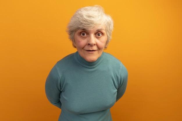 Onder de indruk oude vrouw met blauwe coltrui die de handen achter de rug houdt en naar de voorkant kijkt geïsoleerd op een oranje muur met kopieerruimte