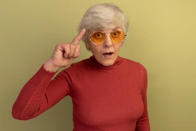 Onder de indruk oude vrouw met een rode coltrui en een zonnebril die een denkgebaar doet geïsoleerd op een olijfgroene muur met kopieerruimte