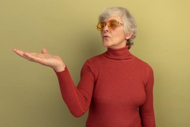Onder de indruk oude vrouw met een rode coltrui en een zonnebril met een lege hand die ernaar kijkt