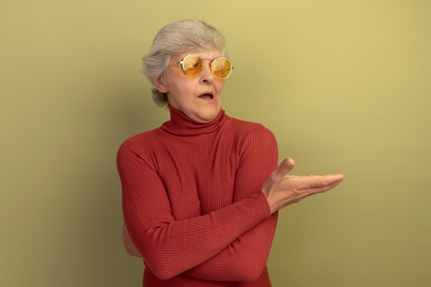 Onder de indruk oude vrouw met rode coltrui en zonnebril kijkend en wijzend met de hand naar de zijkant geïsoleerd op olijfgroene muur met kopieerruimte