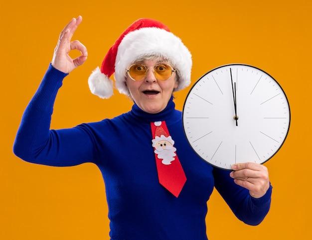 Onder de indruk oudere vrouw in zonnebril met kerstmuts en santa stropdas houdt klok en gebaren ok teken geïsoleerd op oranje muur met kopie ruimte