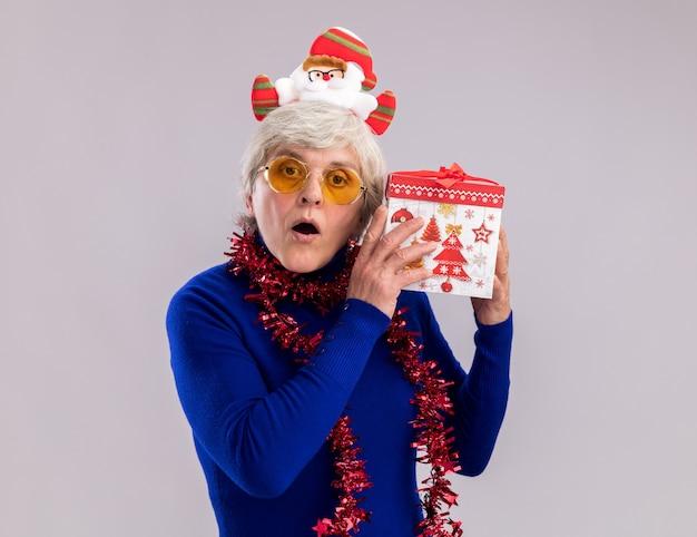 Onder de indruk oudere vrouw in zonnebril met santa hoofdband en slinger om nek houdt kerstcadeaudoos dicht bij oor geïsoleerd op een witte muur met kopieerruimte