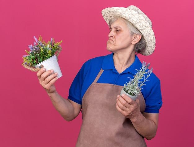Onder de indruk oudere vrouwelijke tuinman die een tuinhoed draagt en naar bloempotten kijkt