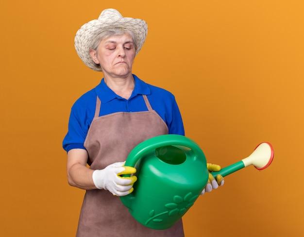 Onder de indruk oudere vrouwelijke tuinman met een tuinhoed en handschoenen die een gieter vasthoudt en kijkt die op een oranje muur is geïsoleerd met kopieerruimte