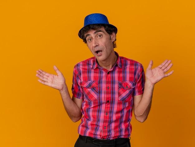 Onder de indruk partijman van middelbare leeftijd die partijhoed draagt die kant bekijkt die lege handen toont die op oranje muur worden geïsoleerd