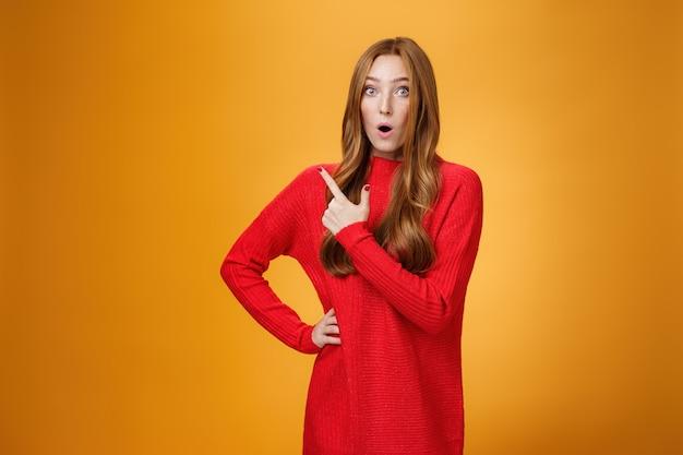 Onder de indruk roodharig meisje reageert op geweldige ongelooflijke promotie wijzend achter of op de linkerbovenhoek vouwende lippen starend naar de camera verbaasd en verrast over oranje achtergrond